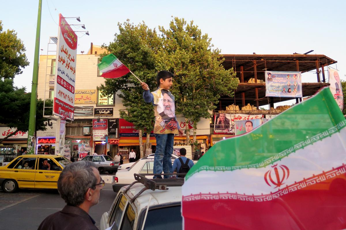 A boy waves an Iranian flag at a rally in Qazvin on Wednesday for the conservative cleric Ebrahim Raisi, the presidential candidate pictured on the boy's shirt.
