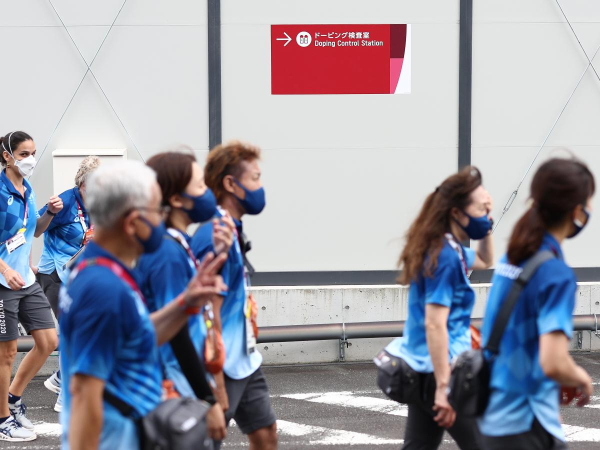A group of Tokyo Olympics volunteers walks past a doping control station, near to the Izu Velodrome cycling venue on Monday.