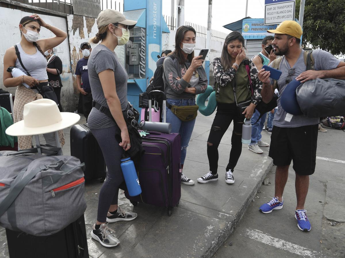 Tourists from the United States wait outside the closed Jorge Chavez International Airport for a member of the U.S. Embassy to escort them to a flight back to the U.S., in Callao, Peru, on March 20. It was the fifth day of a state of emergency decreed by