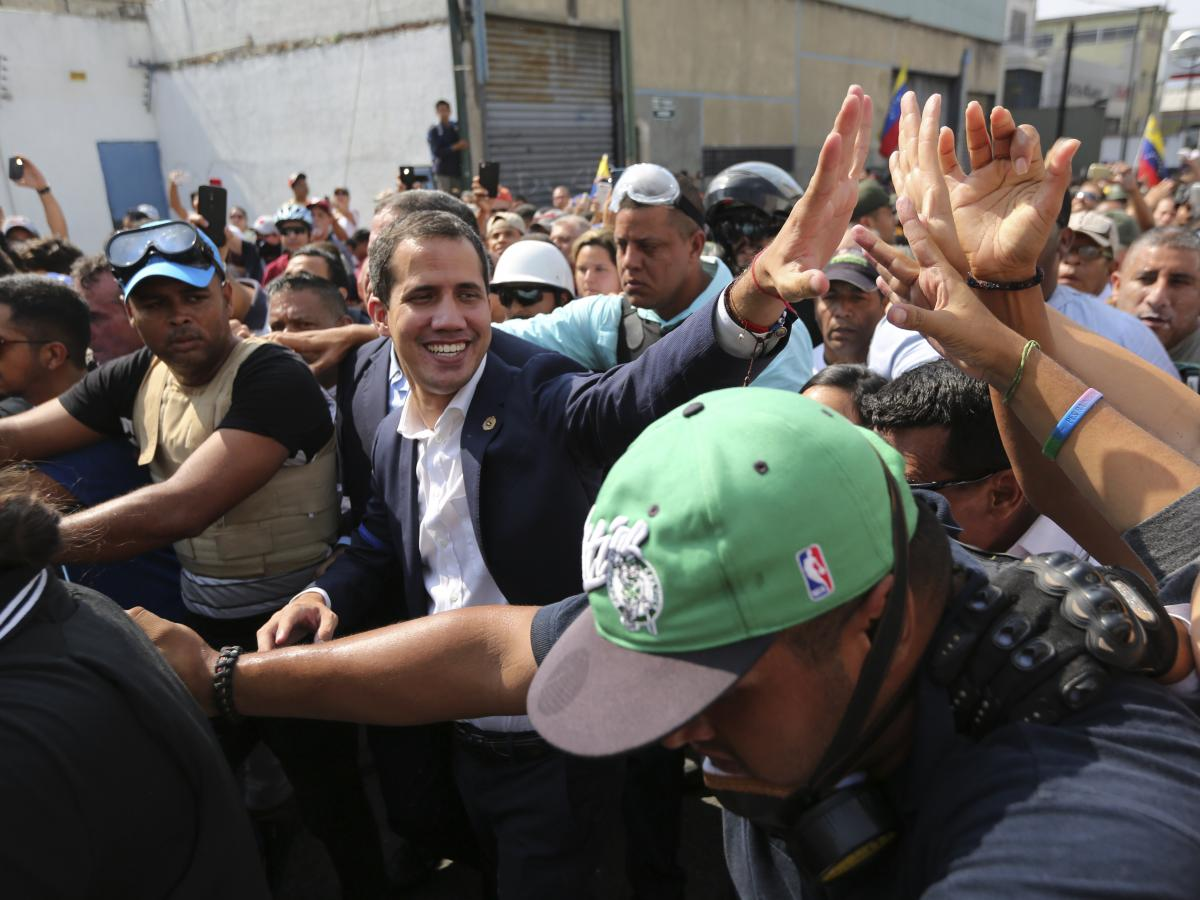 Venezuelan opposition leader Juan Guaidó greets supporters in Caracas, Venezuela, Tuesday. He took to the streets with a small contingent of armed troops and called for the military to rise up and oust President Nicolás Maduro.