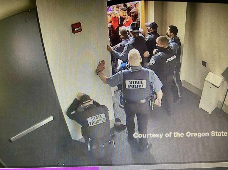 Surveillance video captured Dec. 21 at the Oregon State Capitol shows a crowd of protesters trying to fight their way past Oregon State Police troopers.