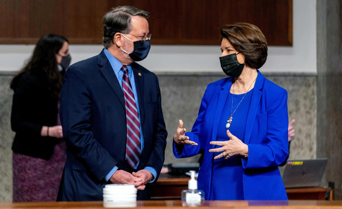 Chairman Sen. Gary Peters., D-Mich., and Chairwoman Amy Klobuchar, D-Minn., speak before the start of a hearing run jointly by their committees — the Senate homeland security and rules panels, respectively.