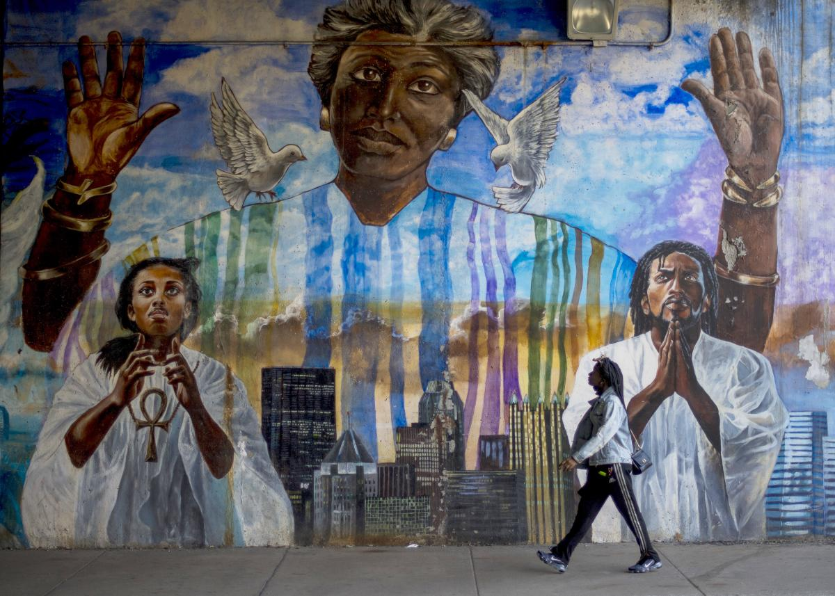 Sheridan Newsome, 21, walks by a mural in Pittsburgh's Homewood neighborhood. Despite receiving the consistent support of Black communities, many voters here say Democratic leaders have largely failed to effectively address enduring problems like police v