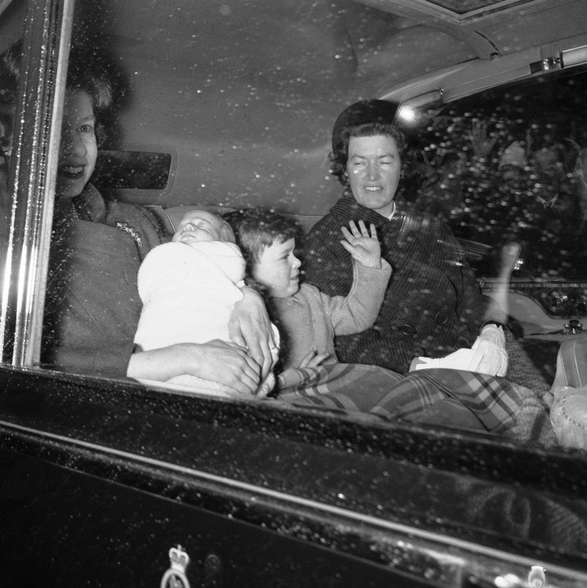 Queen Elizabeth II holds her fourth child, Prince Edward, as they head to Windsor Castle with Prince Andrew in 1964.