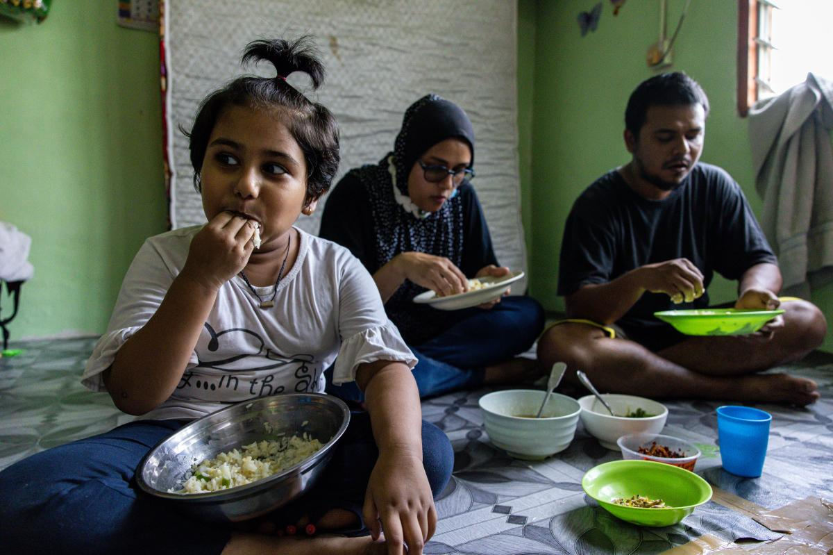 Mohd Ali, right, of Selangor, Malaysia, lost his job due to the pandemic. The family's favorite foods — fried chicken, eggs, fruit and bread — are now typically out of reach. When they can afford chicken, they give most of it to their daughter, Hosna.