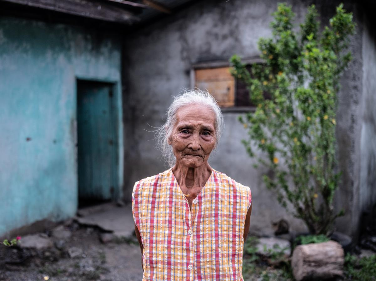 Gloria Hernandez, 82, stands outside her home in Aliaga, a village in the Philippines, where she lives with her daughter and grandsons. During the pandemic, she has been struggling to afford fresh meat and fish.