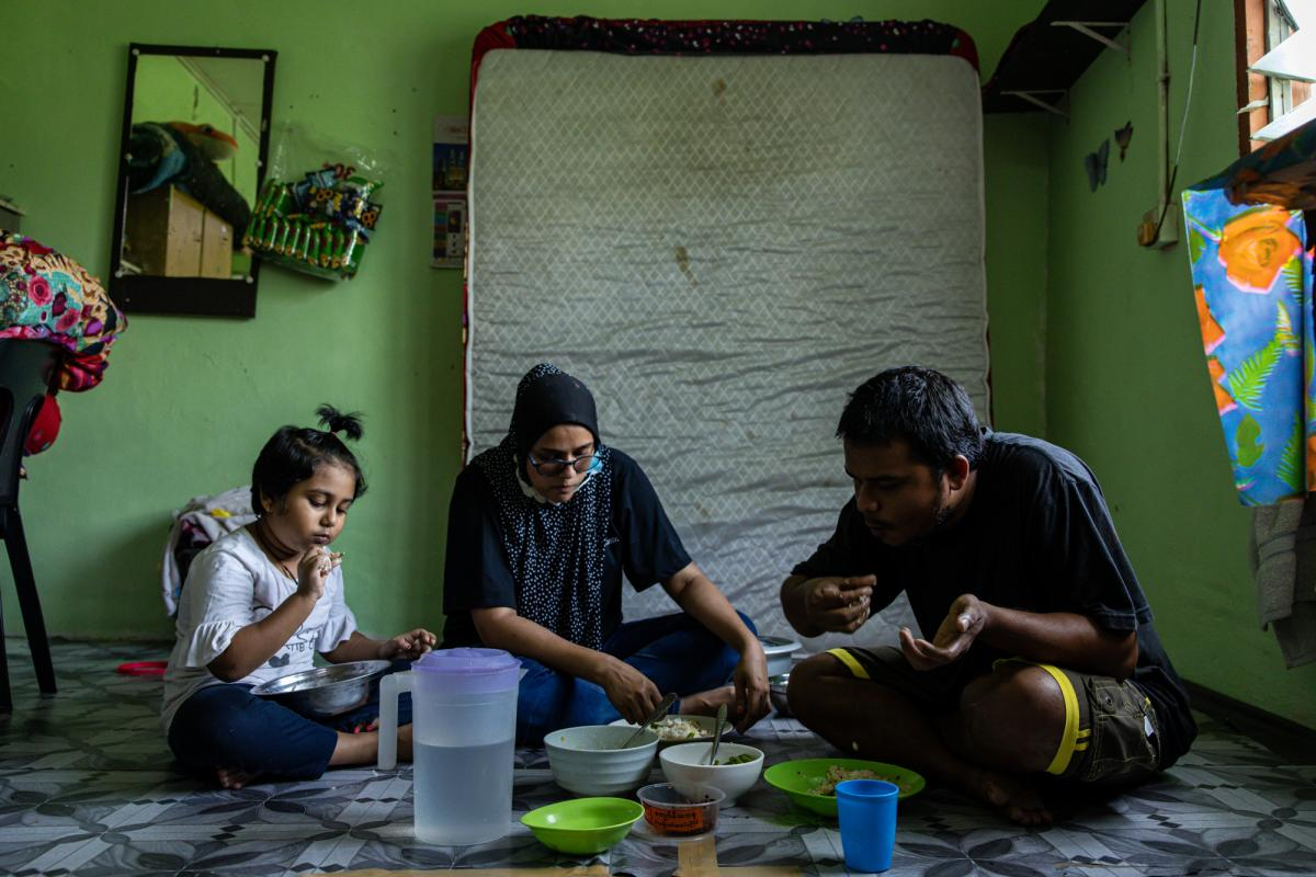 Mohd, right, eats with his wife, Tawhirah, center, and their daughter Hosna, left. Tawhirah is in her first trimester of pregnancy.
