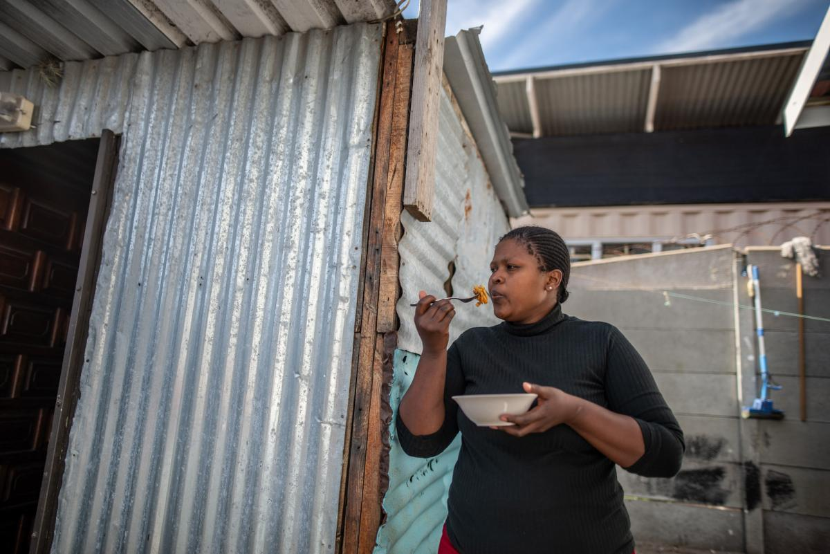 """Aviwe Maphini, 30, eats pasta with canned sardines in front of her home in Cape Town, South Africa. The mom of two was working as a lawyer before the pandemic hit. When she lost her job, she says, """"The first thing I thought of was my kids."""""""