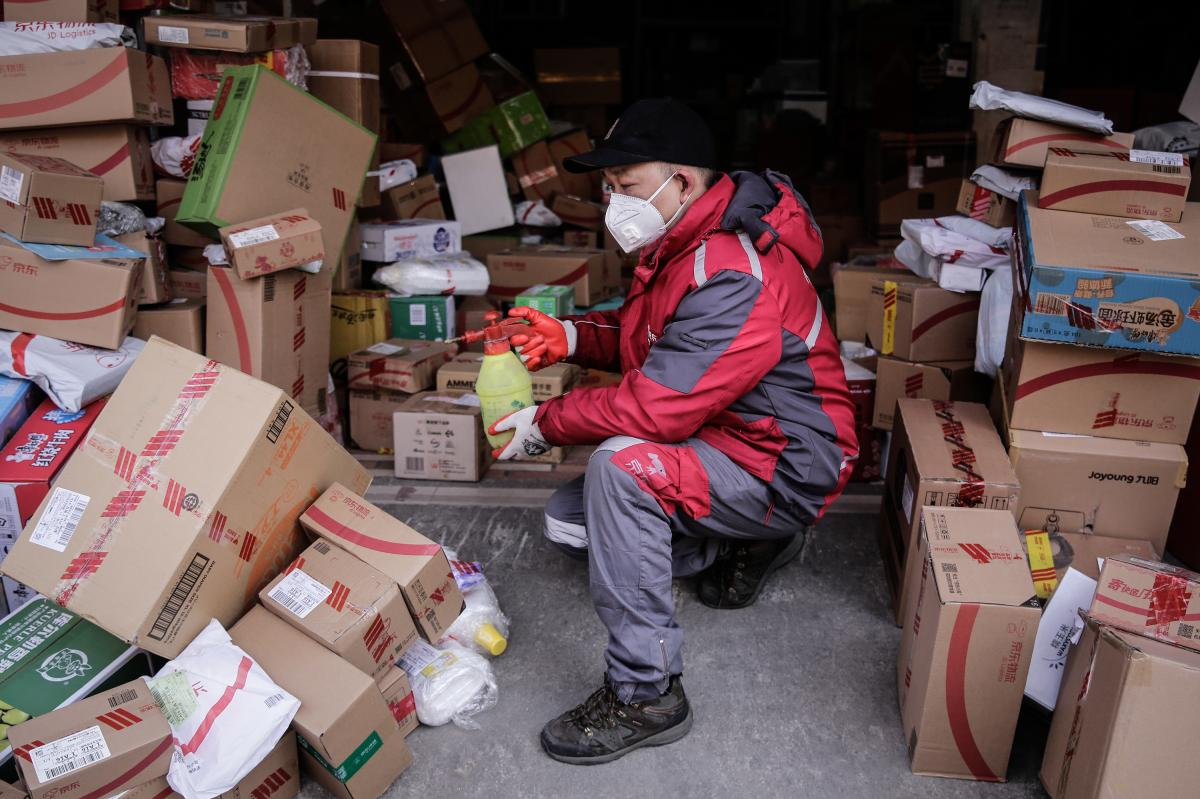 A courier uses alcohol to disinfect packages in order to prevent any potential coronavirus pathogens from spreading to themselves and customers.