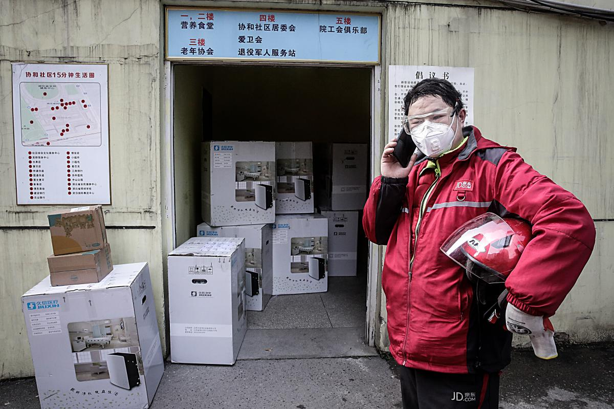 A delivery worker makes a phone call. Usually, couriers deliver packages right to a customer's door, according to Ling Cao, a representative from JD Logistics, one of China's largest delivery companies. But to avoid unnecessary contact, couriers have been