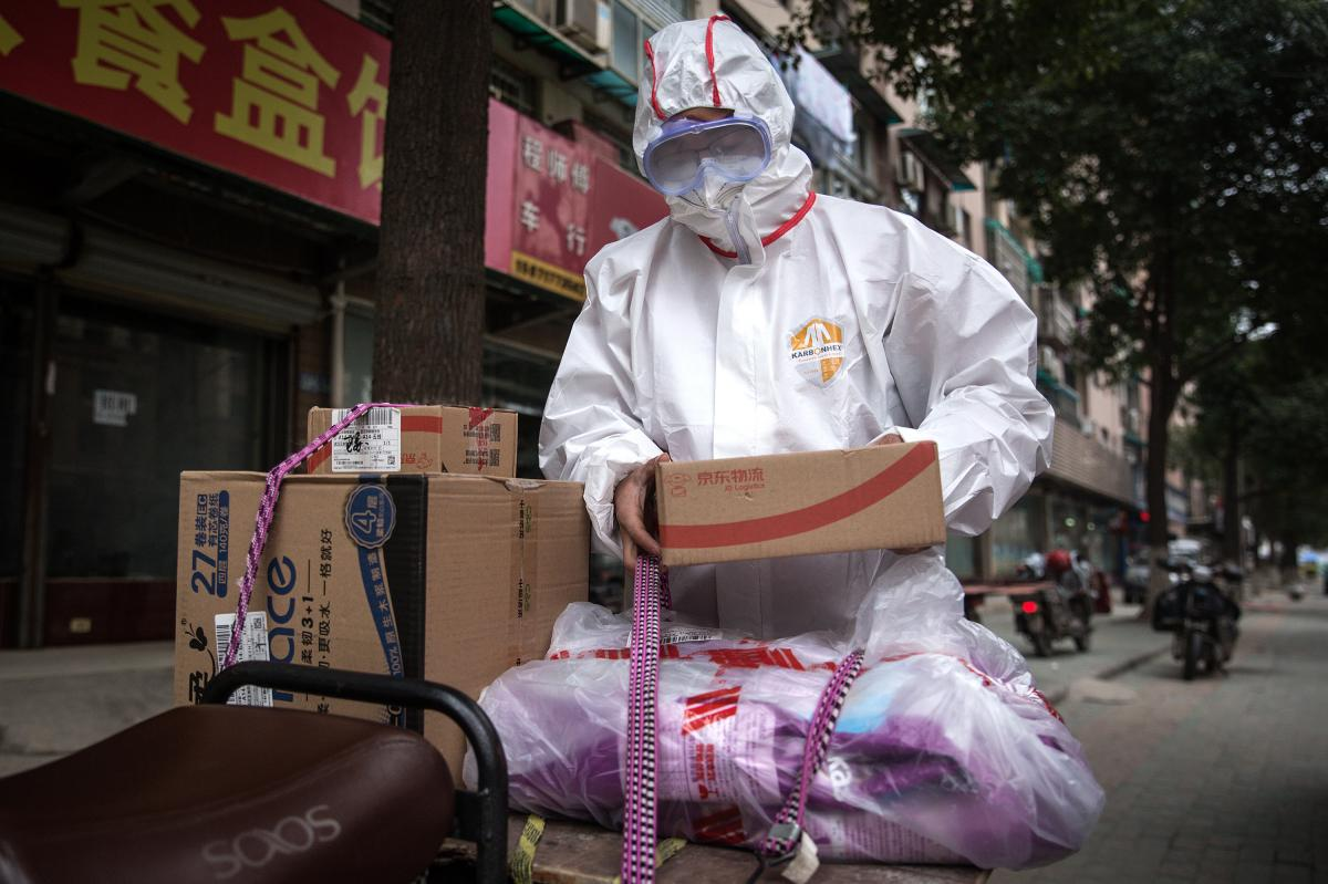 A worker in protective clothing with a package. In addition to encouraging couriers to wear this gear, the Chinese Center for Disease Control and Prevention has published a guide for the deliverymen, encouraging them to wash their hands and disinfect them
