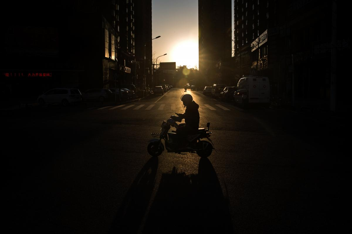 A courier at dusk. According to Chinese state media, people have mixed feelings about the couriers. Some feel grateful to them for providing supplies during this time of crisis. Others are afraid the workers may transmit the virus because they're travelin