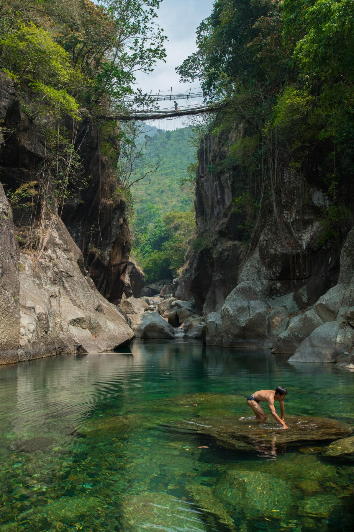 A villager crosses a root bridge over a deep river valley while a man takes a bath in the river's turquoise water. During monsoon season, the water level rises by a few feet, and it becomes impossible to cross the river in the absence of such bridges.