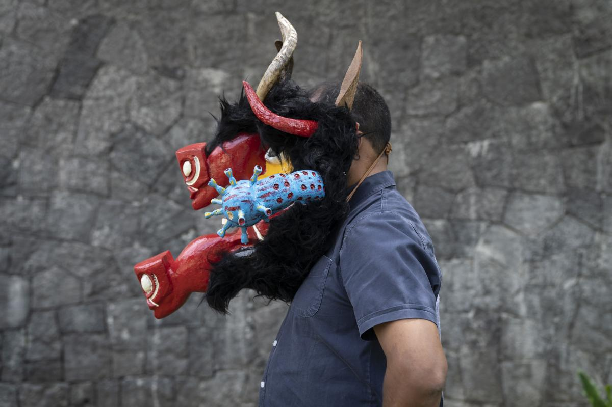"""Carlos Dávila, subdirector of bachelor degrees at the National School of Anthropology and History, poses with the mask """"The Devil of Teloloapan,"""" by Fidel Puente from Teloloapan, Guerrero, Mexico."""