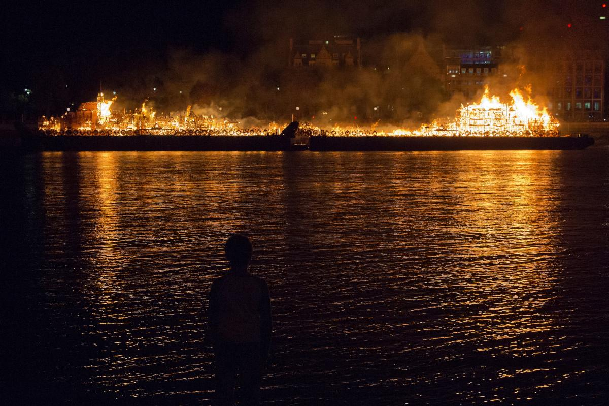 A person stands on the shore watching a replica of 17th-century London burning on a barge in the Thames on Sunday. In 1666, an inferno destroyed most of the inner city — a bustling, congested maze of tightly-packed wooden houses, surrounded by walls tha