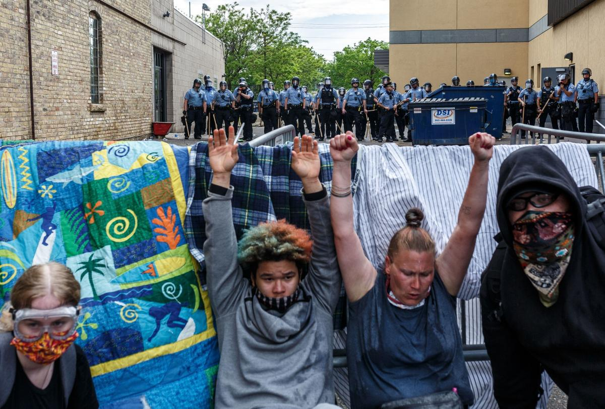 Protestors hold their hands up as they cry from from tear gas during a demonstration in a call for justice for George Floyd following his death, outside the 3rd Police Precinct on May 27 in Minneapolis, Minn.