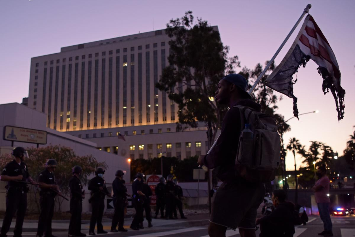 A man faces a row of police holding a burnt upsidedown U.S. flag as protesters gather in downtown Los Angeles.