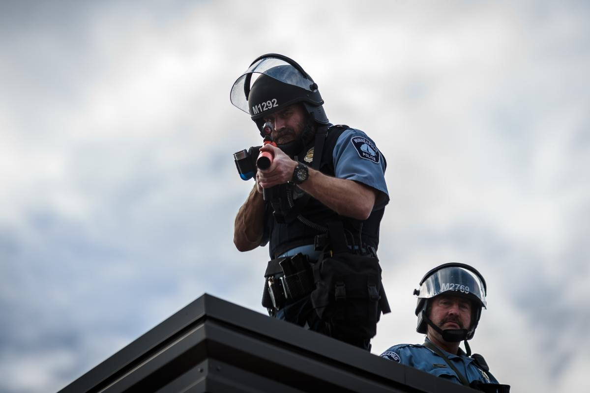 Two police officers stand on the roof of the Third Police Precinct holding a projectile launcher during a demonstration in a call for justice for George Floyd following his death.