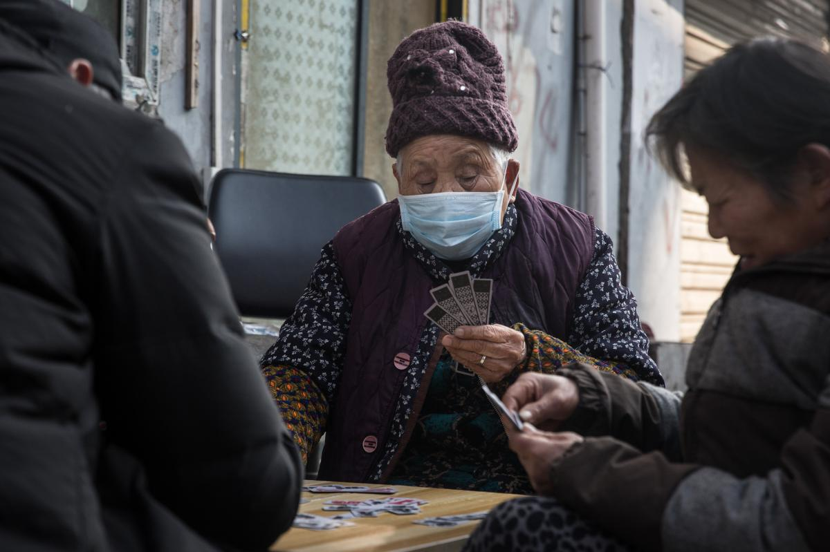 People play a game of cards outdoors. Wuhan's government has forbidden large gatherings.