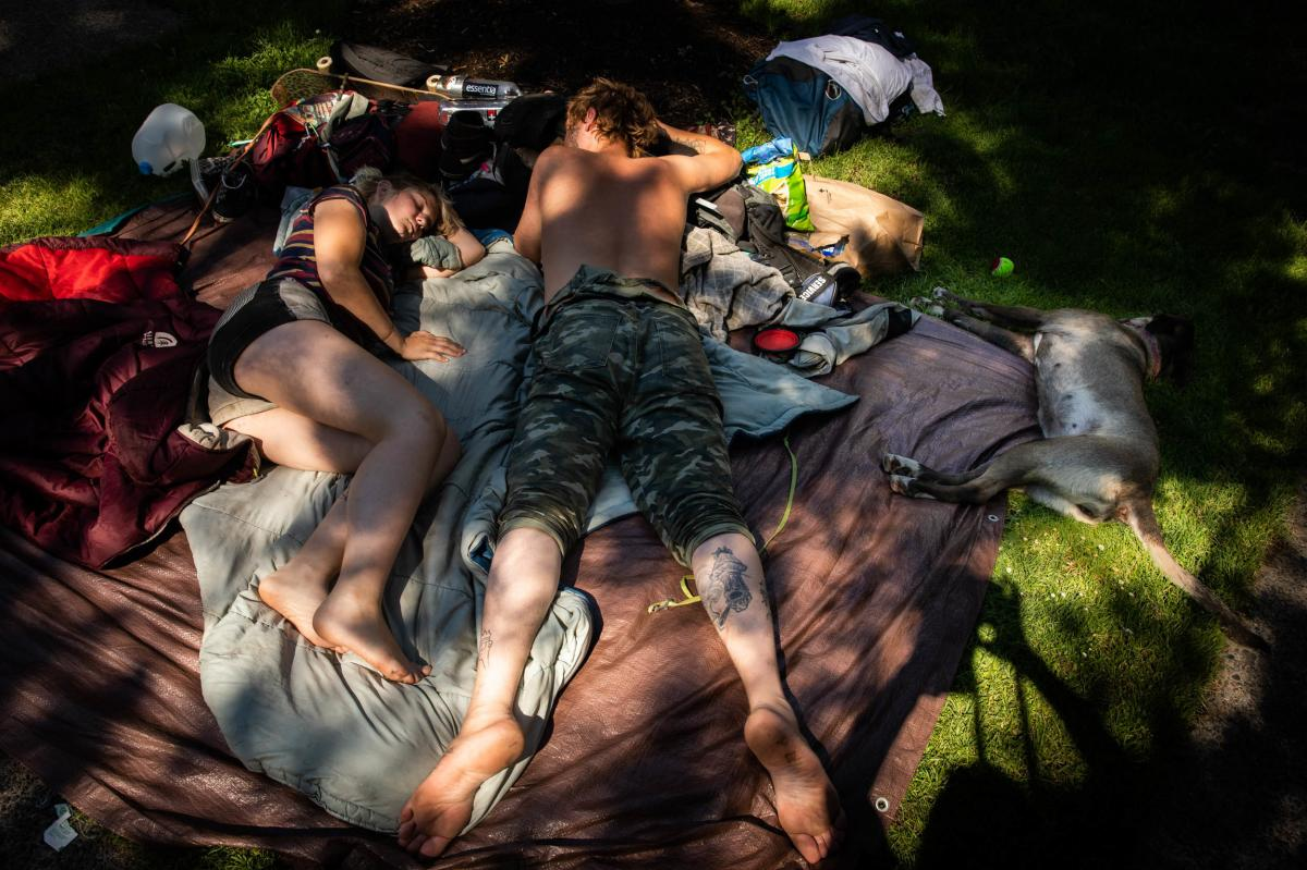 Portland recorded three of its hottest days in history last Saturday and this Sunday and Monday. Here, a couple and their dog lay in the shade during the heat wave.