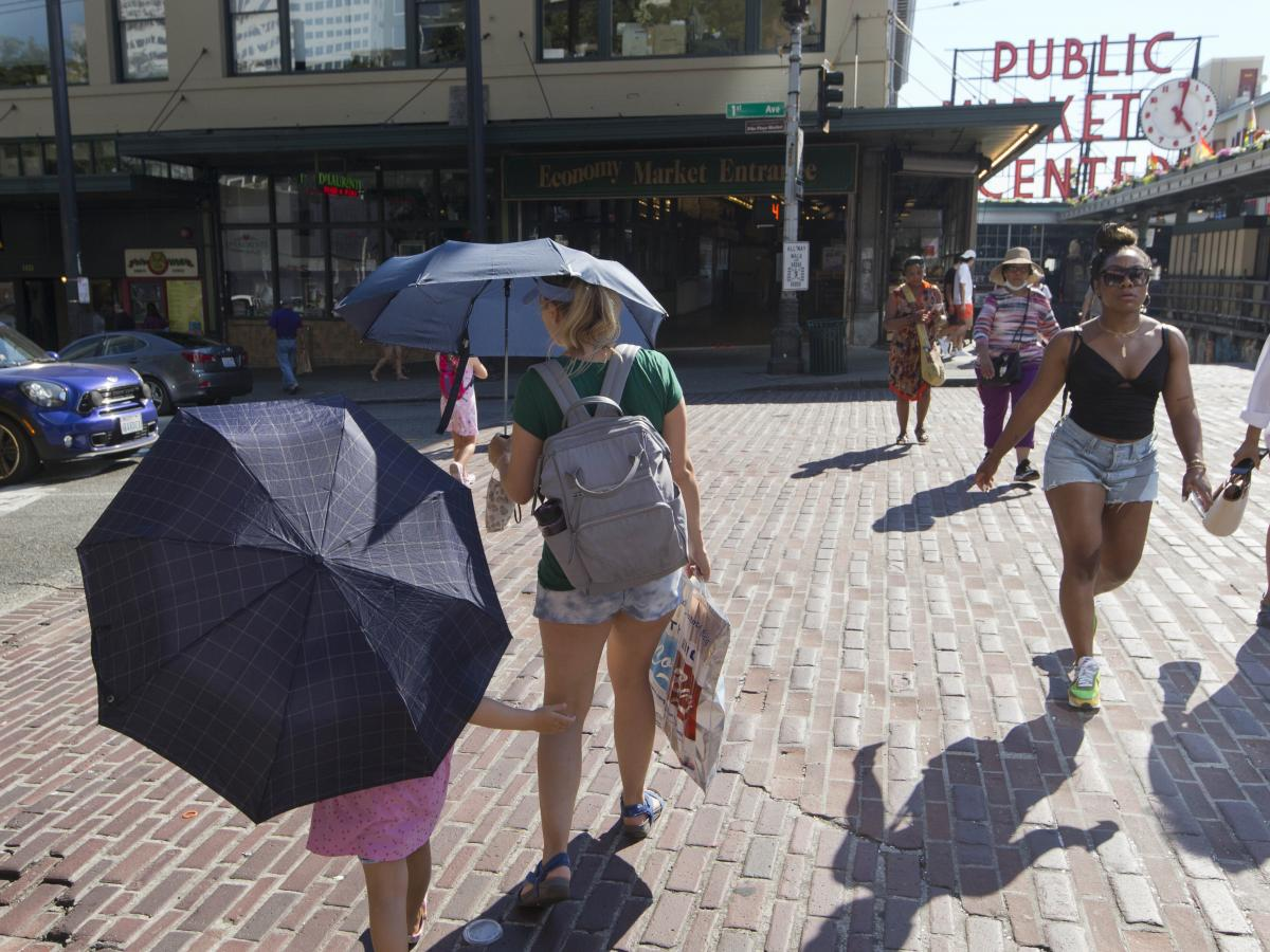 Seattle reached 108 degrees on Monday during the heat wave in the Pacific Northwest. Here, a mother and daughter carry umbrellas to shield from the sun.