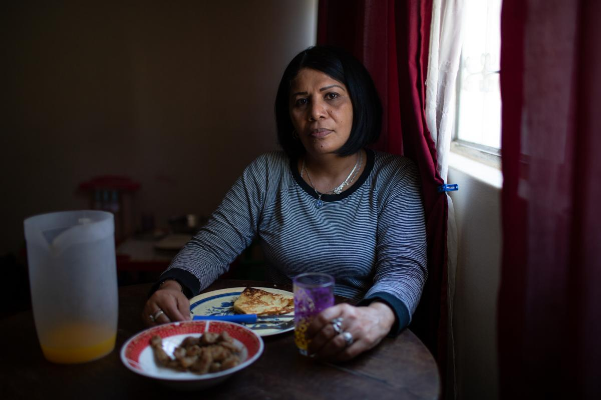 Yroné Camelia Araujo Barreto, a 50-year-old Venezuelan migrant living in Quito, Ecuador, at the dining room table. She is eating a traditional Venezuelan dish of cachapa, round dough made from corn, filled with pork. She typically eats two meals a day if