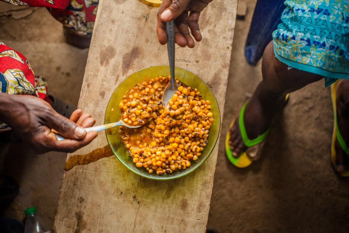 """Femi Oyekan Moses, left, and his wife Mary share a dish of boiled beans and corn at their home in Oyo, Nigeria. Before the pandemic, he says, """"I used to give my wife enough to get bags of rice, garri [cassava flour], pepper, fish and meat."""""""