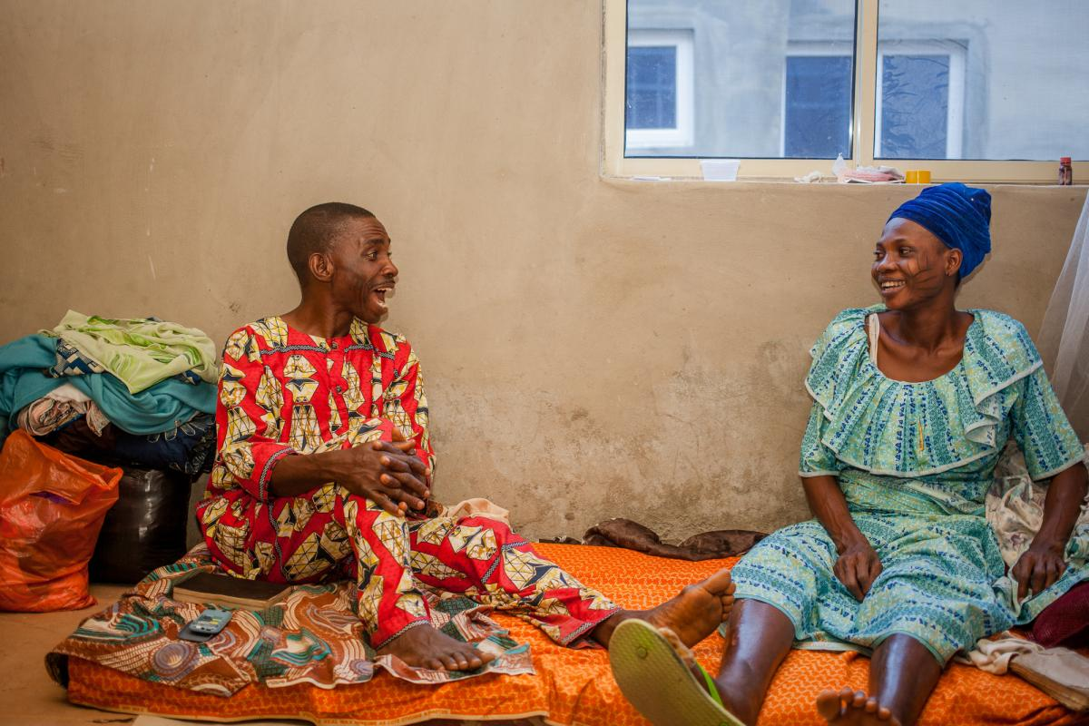 Femi and Mary sit together at home. Femi says he remains optimistic the family will return to the life they had before the pandemic. For now, he says, the support of friends, family and church helps them cope.