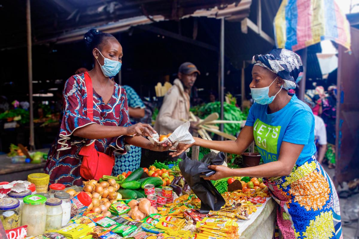 Kiali Onzhe Ngssakhes, right, buys vegetables and spices at Talangai Market in Brazzaville, Republic of Congo. The 45-year-old single mother, who is HIV positive, had to stop selling grilled meat due to the pandemic — and now can't buy as much food as s