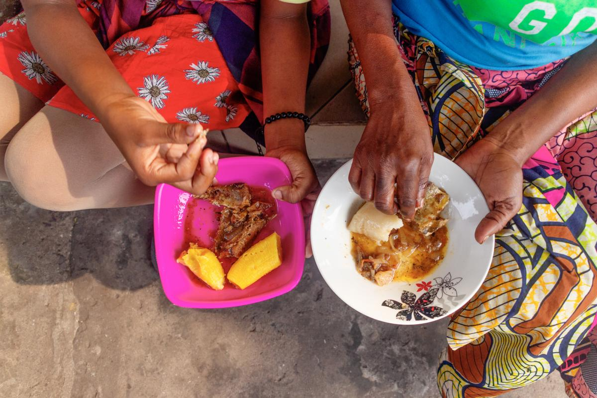 Ngssakhes, right, and her 12-year-old daughter, left, eat boiled plantains and fried fish outside their home.