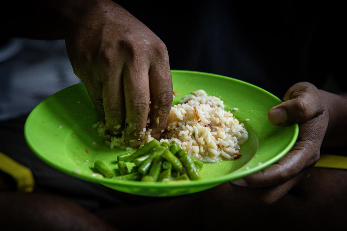 Ali eats a typical Malaysian dish of long beans and rice.