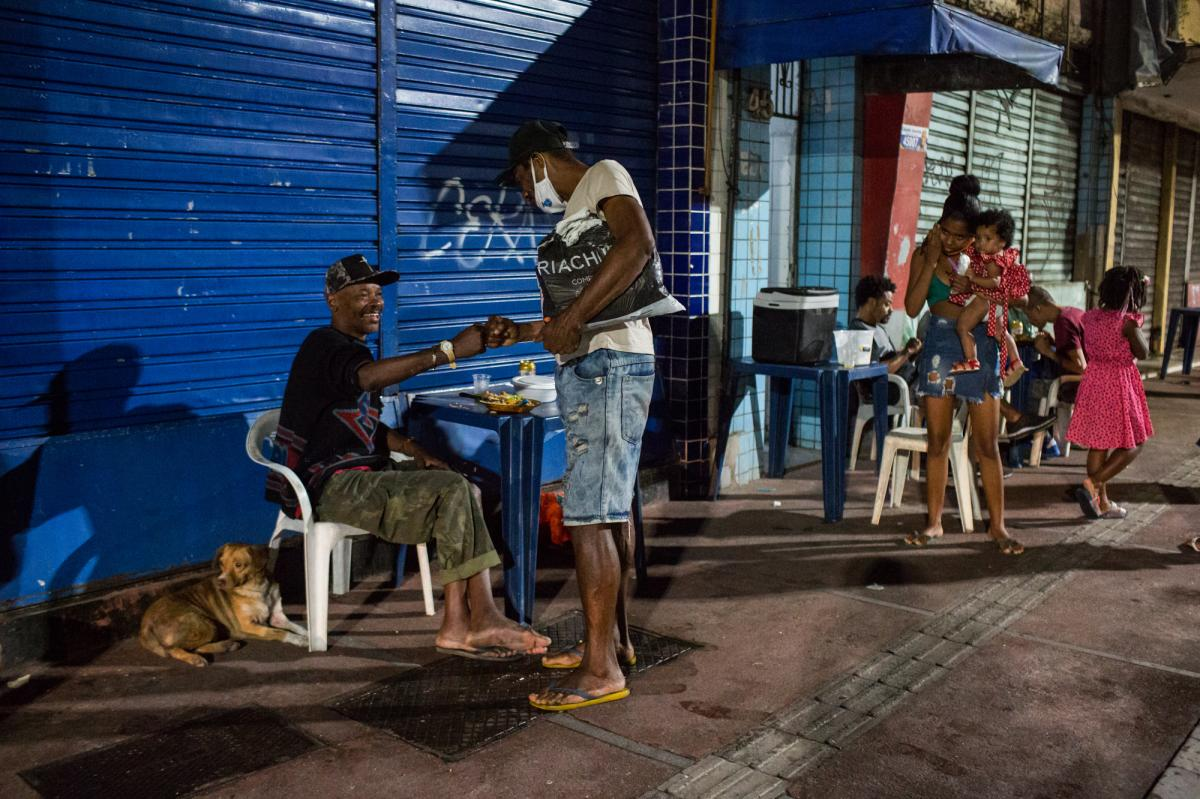 Costa, left, talks to a passerby while eating his meal. Since his wife died a few months ago, he has been living on the streets. Without her income, he can no longer afford their apartment.
