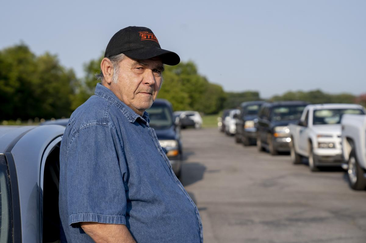 Lloyd Abshier, 70, stands outside his car waiting for a drive-through food distribution event to begin in Columbia, Tenn. Abshier arrived over two hours early to get food for his wife and two kids.