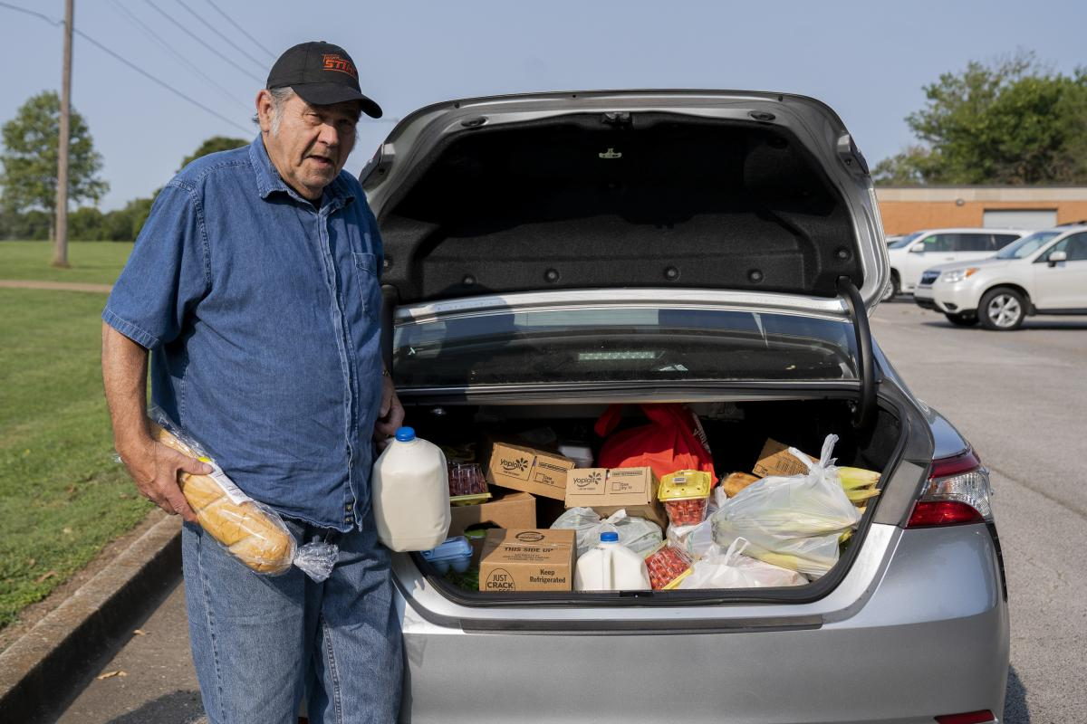 Abshier stands outside his car after receiving groceries from the food bank. The items include milk, yogurt, cherry tomatoes, bread, eggs, bok choy, cabbages, grapes and mini cherry pies.