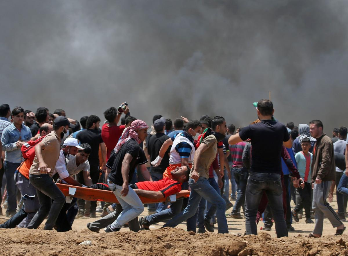 Palestinian men carry an injured protester during clashes with Israeli forces near the border between Israel and the Gaza Strip.