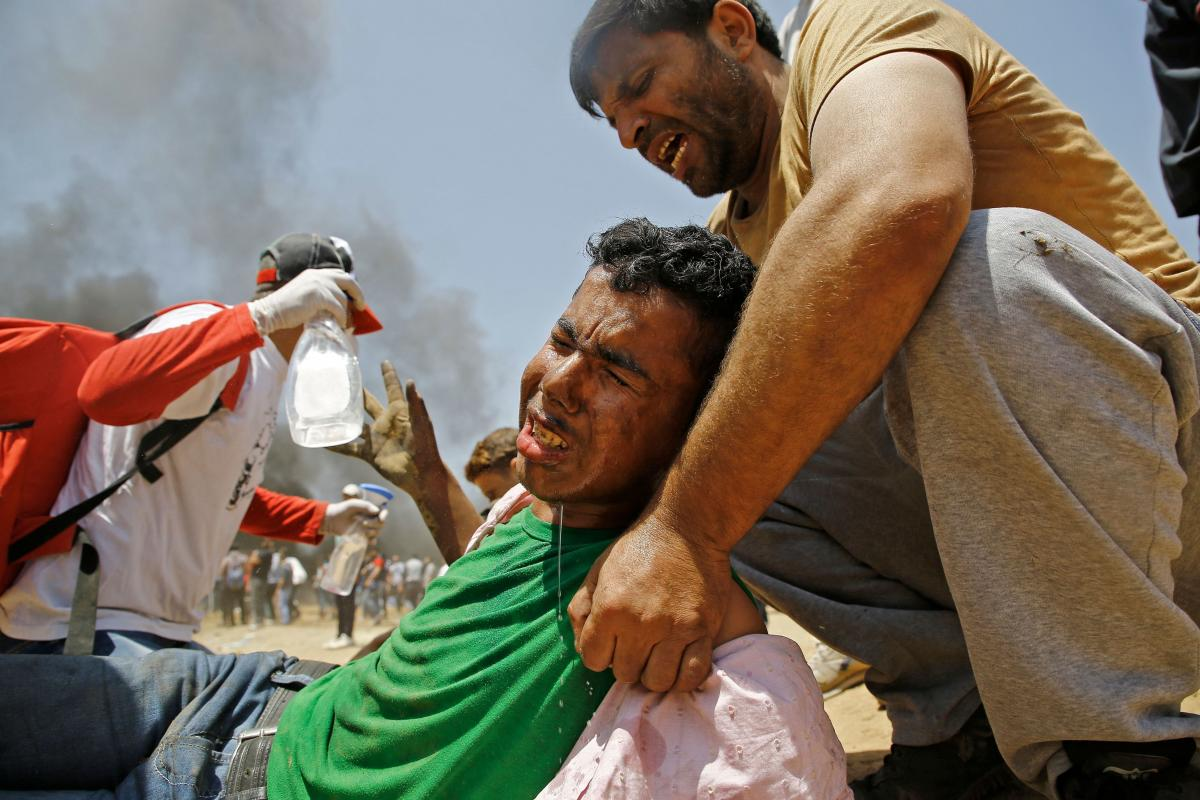 A Palestinian man assists a wounded protestor during clashes with Israeli security forces near the border between Israel and the Gaza Strip.