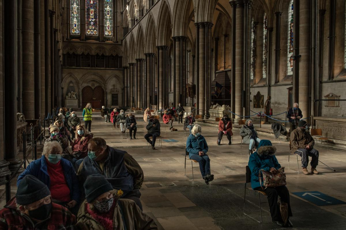 People wait to see if they have a reaction after receiving COVID-19 vaccines at a vaccination center in February at Salisbury Cathedral in Salisbury, England.