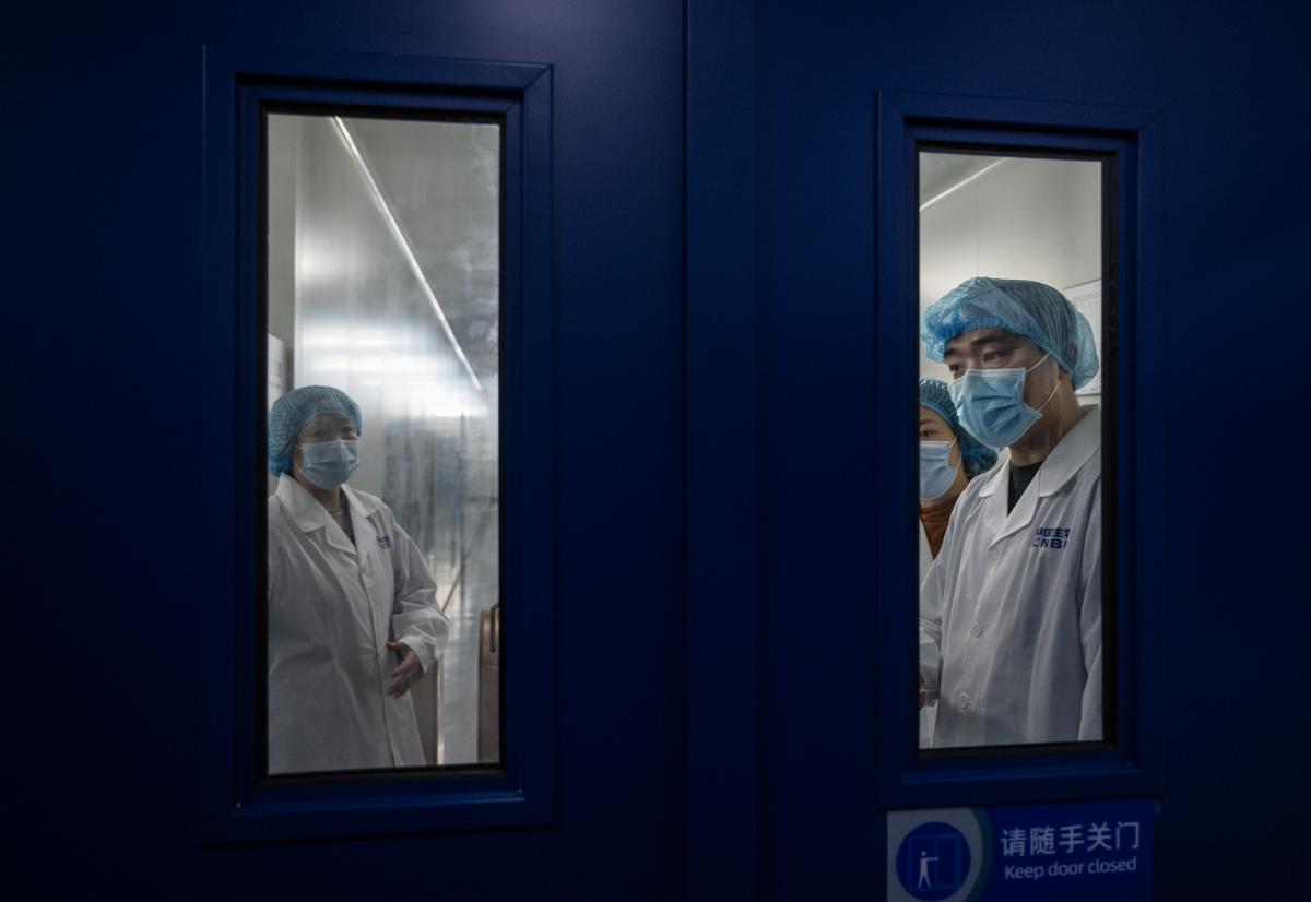 Workers wait to open a secure door in the packaging area of Sinopharm's COVID-19 vaccine during a media tour organized by the State Council Information Office in February in Beijing. Sinopharm is one of China's largest state-owned biotech companies.