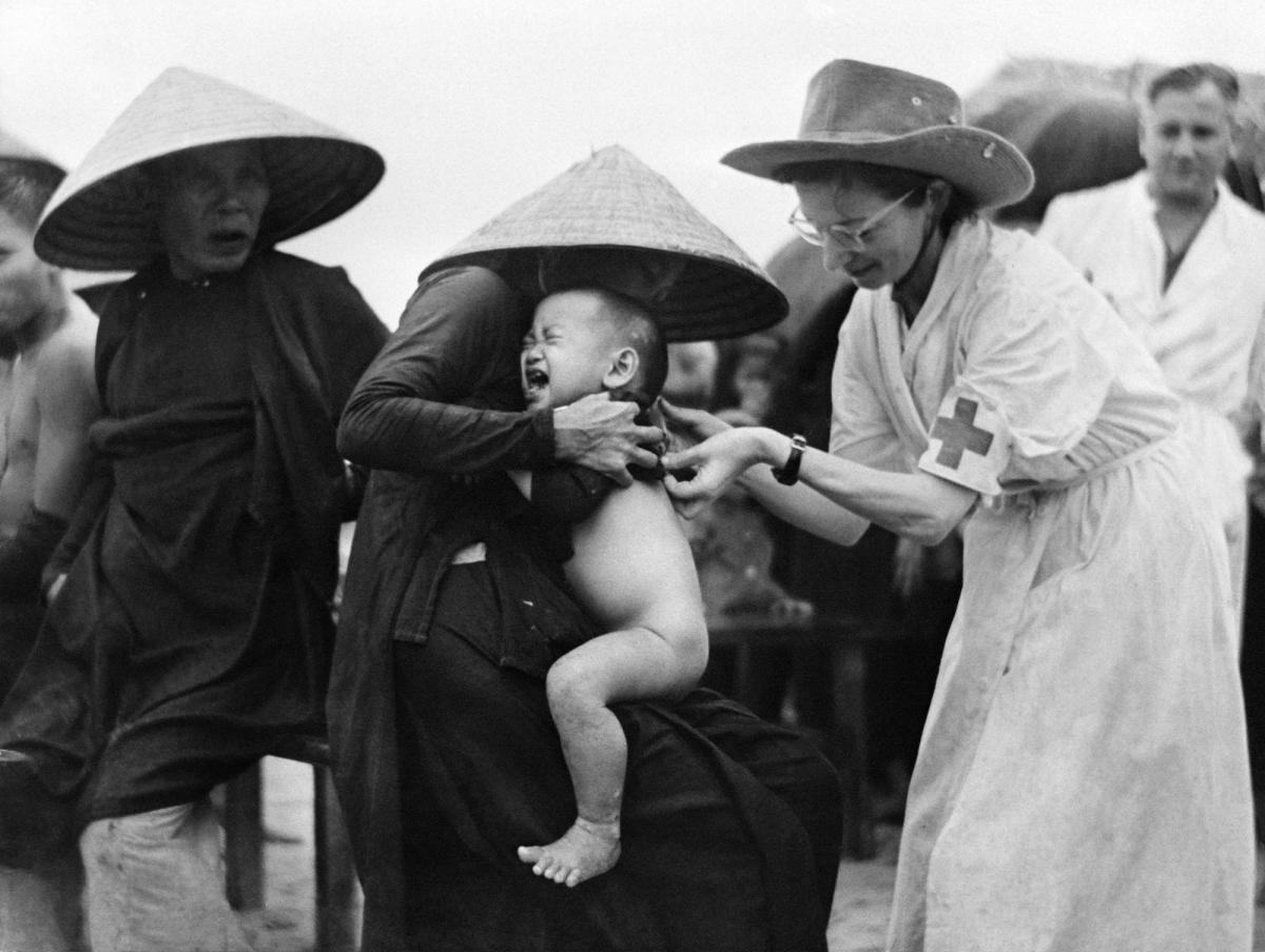 Marie Josette Francou (right), a Red Cross nurse, vaccinates a child against cholera in 1953 in Indochina (now Vietnam).