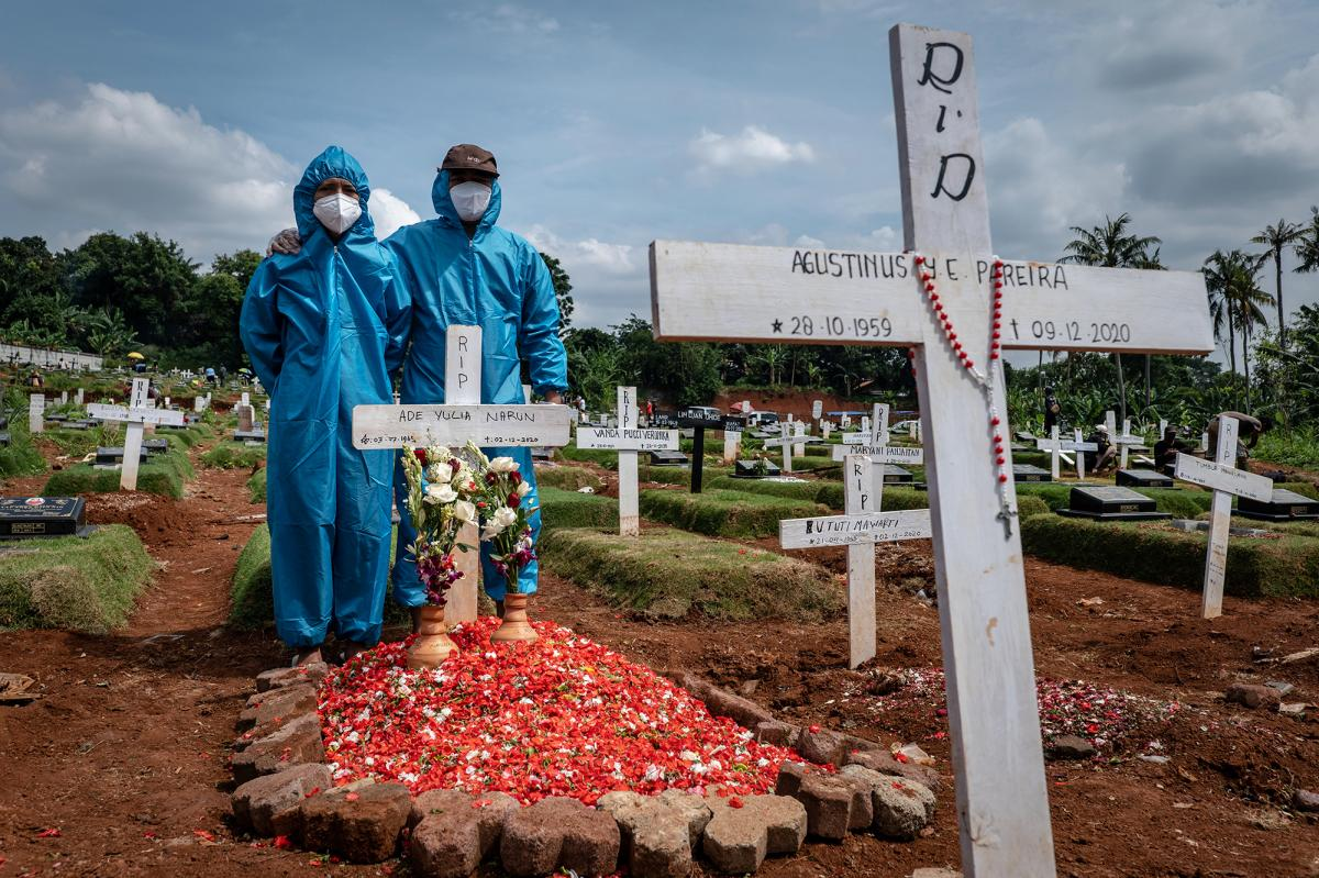 Two men, wearing personal protective equipment, visit the grave of a relative in a public cemetery, reserved for suspected COVID-19 victims, in December in Jakarta, Indonesia.