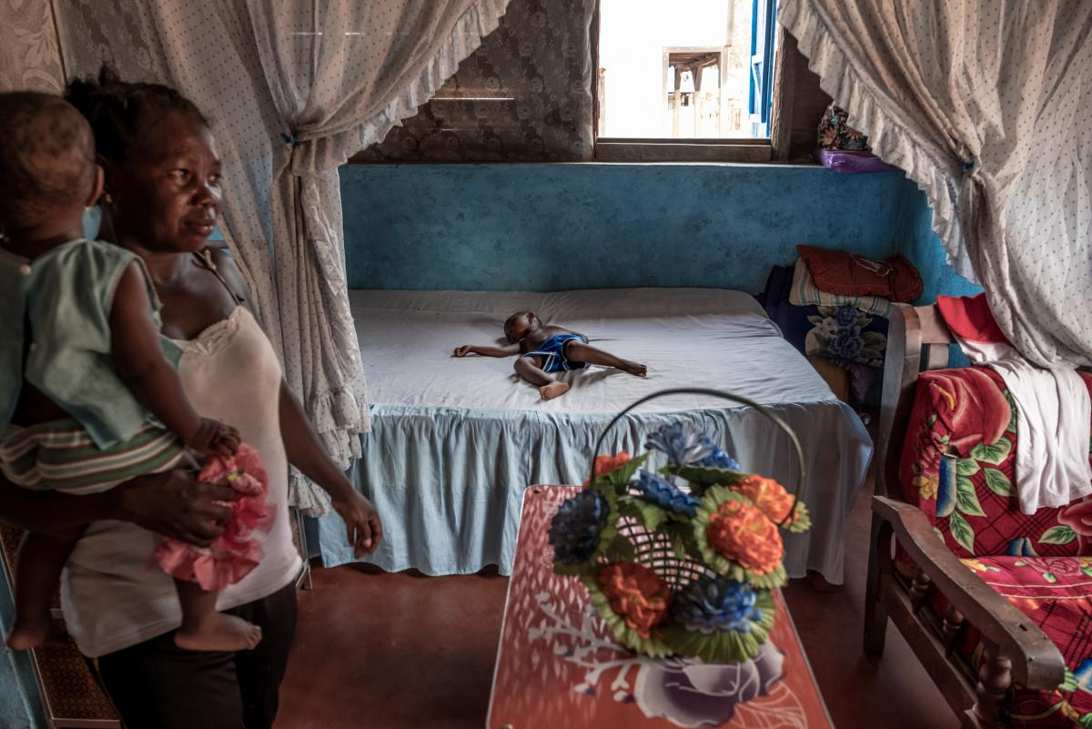 A boy sleeps in a large bed in the spacious home of successful vanilla farmer in Belambo village, Madagascar.