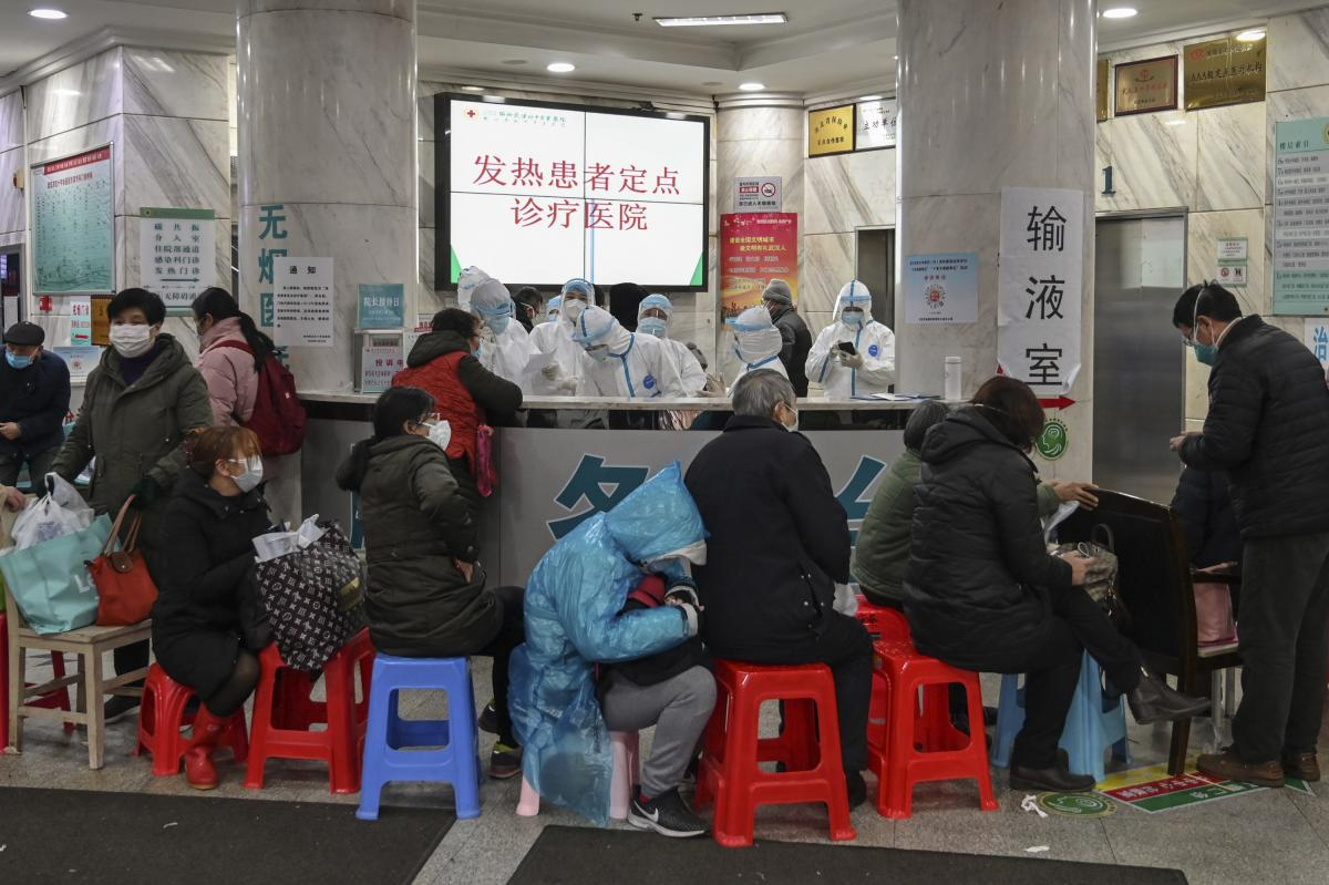 People wait as medical staff wear protective clothing to help stop the spread of a deadly virus which began in the city, at Wuhan Red Cross Hospital in Wuhan on January 24, 2020.