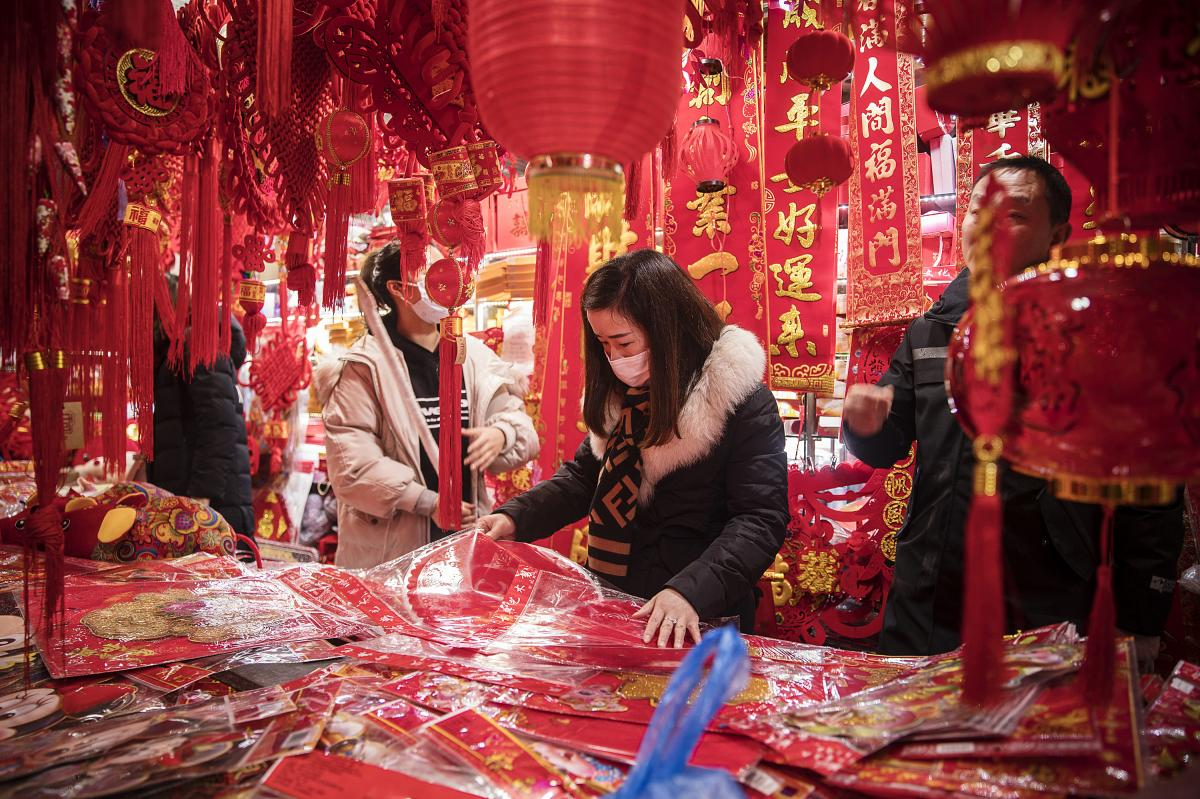 A woman wearing a protective mask shops for festive decorations ahead of the Lunar New Year in Shanghai, China, on Jan. 23, 2020.