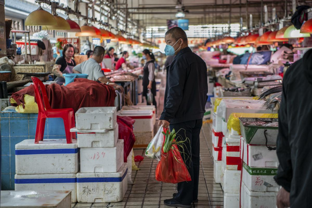 A shopper wearing a face mask walks through a wet market in Shekou the day before the Lunar New Year in the southern coastal city of Shenzhen, China on January 25, 2020.
