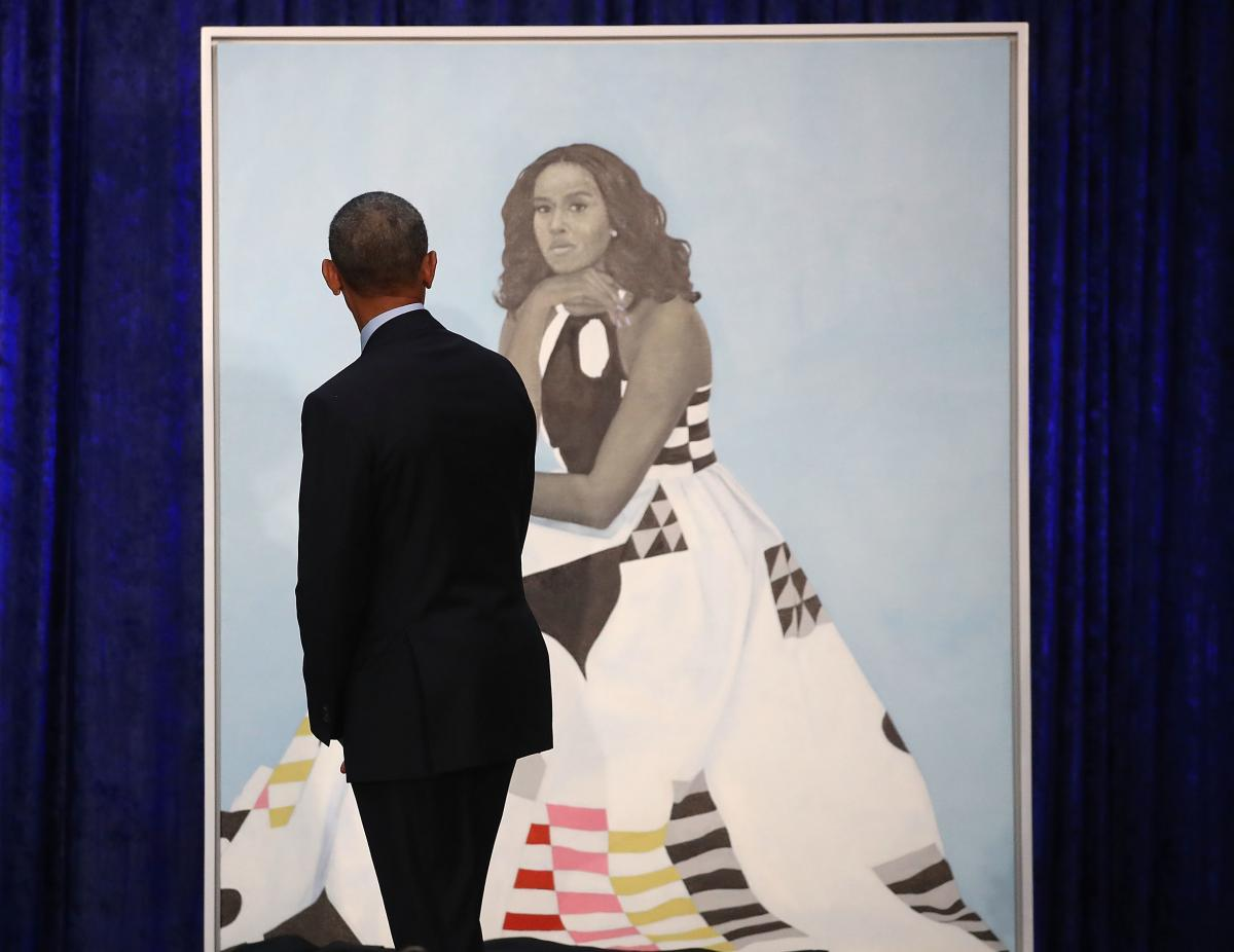 """Barack Obama gazes at his wife's newly unveiled portrait on Monday. The painting of Michelle Obama will be on display through November in the National Portrait Gallery's """"Recent Acquisitions"""" section."""