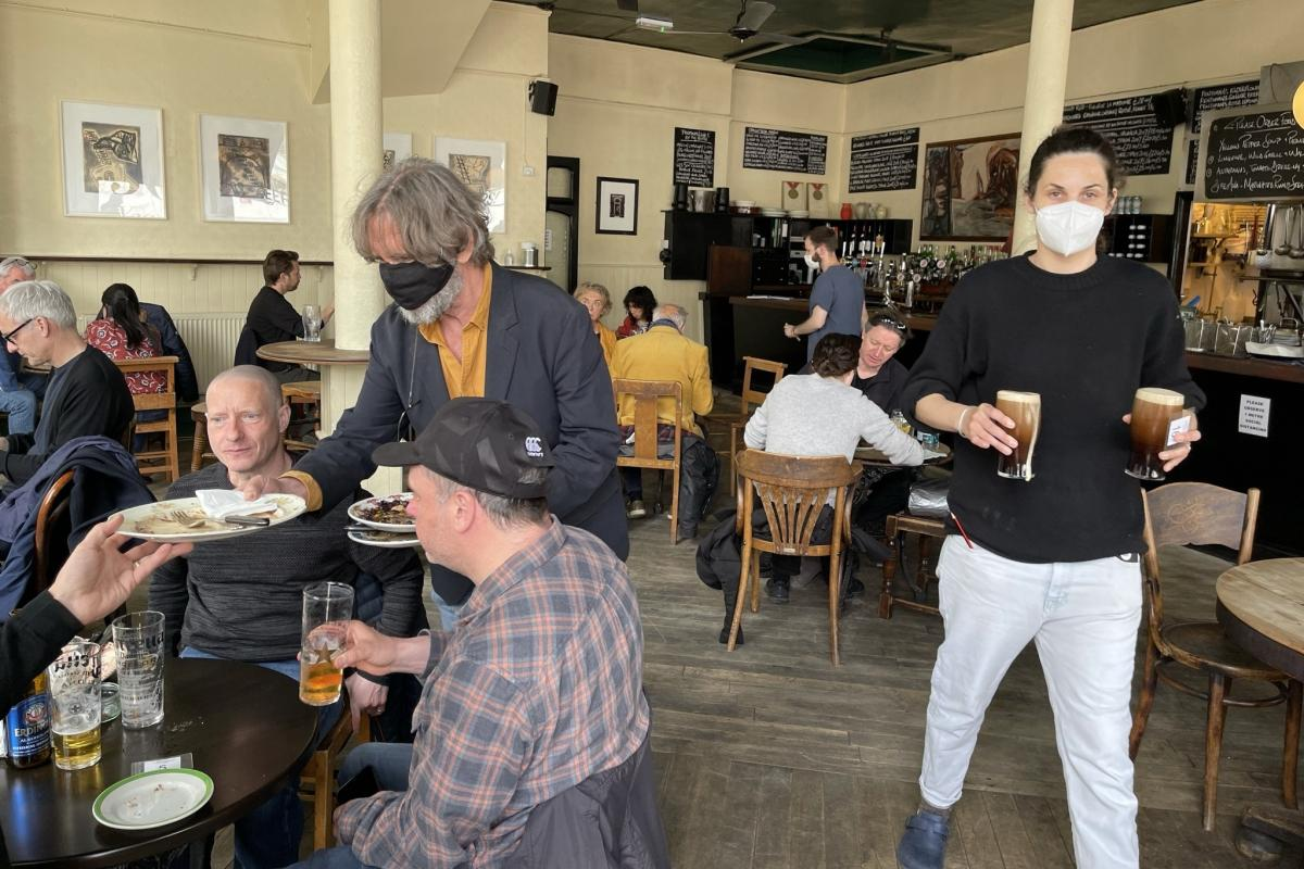 Belben clears plates on the pub's reopening day in May after months of coronavirus lockdown.