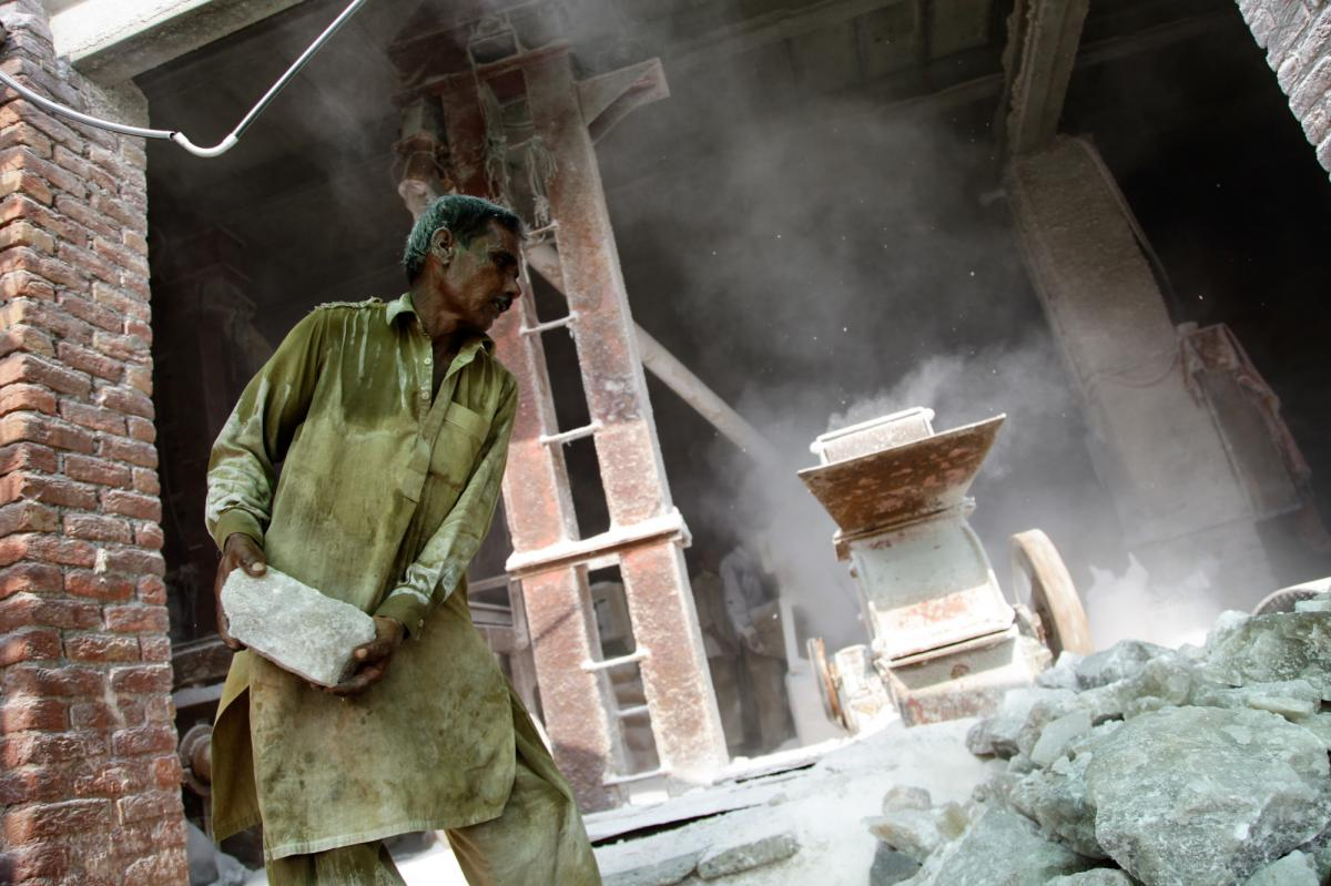 A worker hurls and shovels pink rock salt into a large grinder at a processing plant in Khewra.