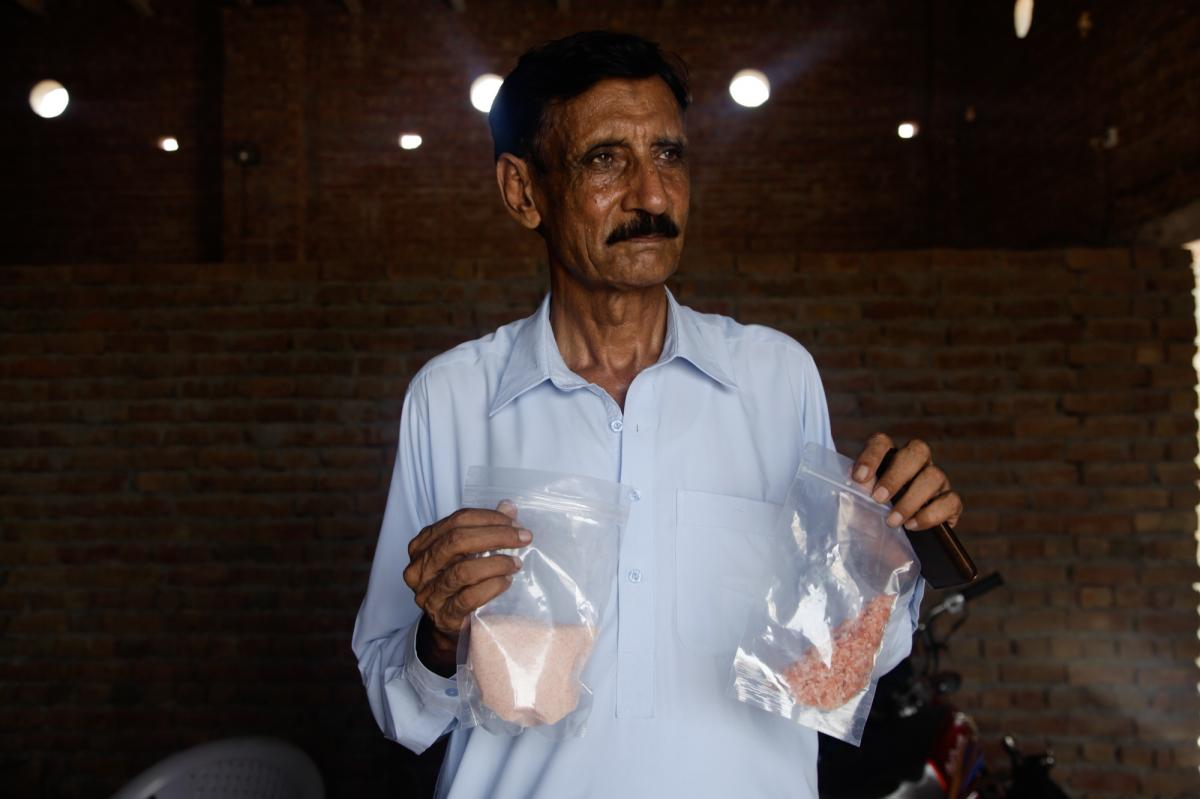 Qaisar Mahmood, a small-time Pakistani salt exporter, holds up two bags of pink Himalayan salt ground up to various consistencies. His business has been devastated by the ban on exports to India, and he says it is a bad idea to force companies to label sa