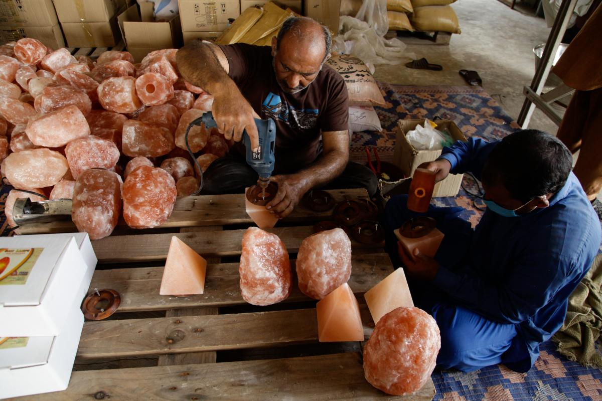 Workers drill wooden bases onto Himalayan salt lamps at a store owned by Niaz Hussain Siddiqui, who exports Pakistani salt products to the United States.