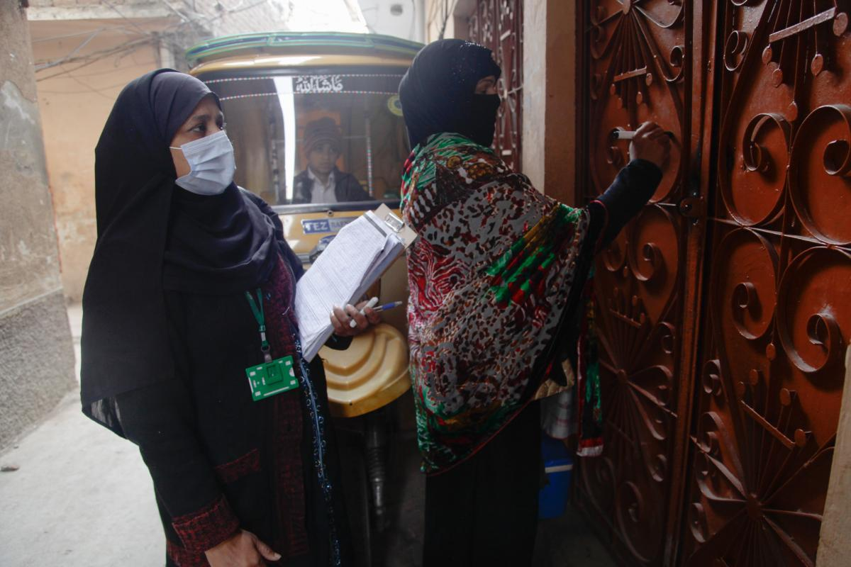 A volunteer working alongside Parveen records details of which children they vaccinated, and on which days, on the door of the family's home. Many doors in Pakistan have similar markings, which let health workers see at a glance how many children are in e